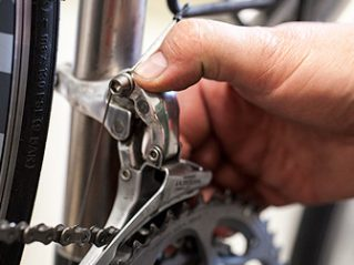 Adjusting a derailleur on one of ExperiencePlus!'s Ti Road bikes. Photo by John Giebler